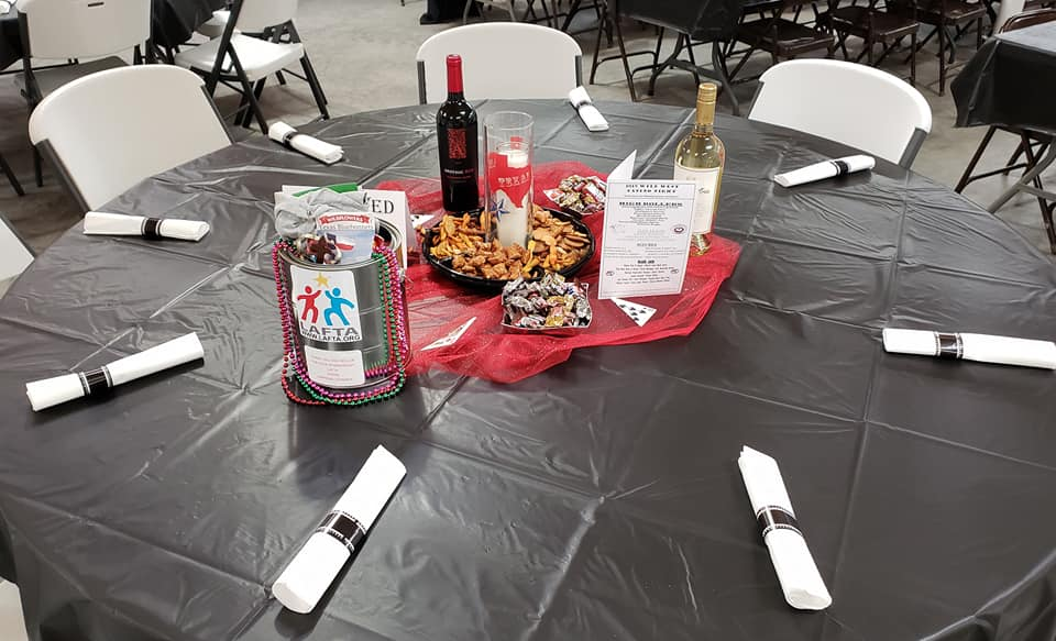 table at event with snacks, wine and promotional items