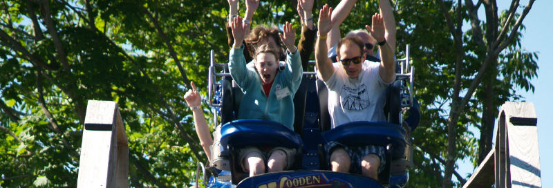 people with hands in the air on roller coaster