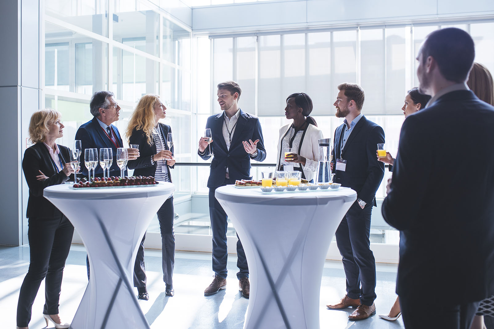 Business coworkers standing in a lobby. They are looking at each other and holding glasses of champagne and juice.