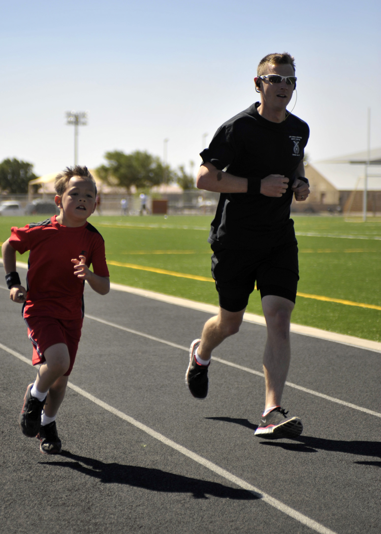 U.S. Air Force Tech. Sgt. Robert Wilson, 27th Special Operations Security Forces Squadron, and son Tyler , 7, sprint to the finish of the two mile race during the America's Kids Run, at Cannon Air Force Base, N.M. May 21, 2011. Sergeant Wilson and Tyler were two of roughly 70 parents and children that competed in the morning's events. (U.S. Air Force photo by Airman Ericka Engblom)