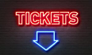 Tickets neon sign on brick wall background