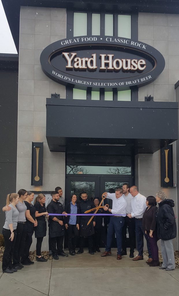 Yard House Willow Grove manager cuts the ribbon at their grand opening using the giant EMCCC scissors.