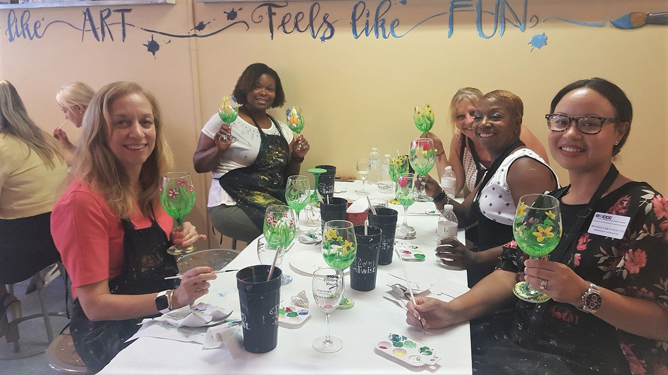 EMCCC Women's Group enjoys painting wine glasses at Painting With a Twist Jenkintown at a summer networking event.