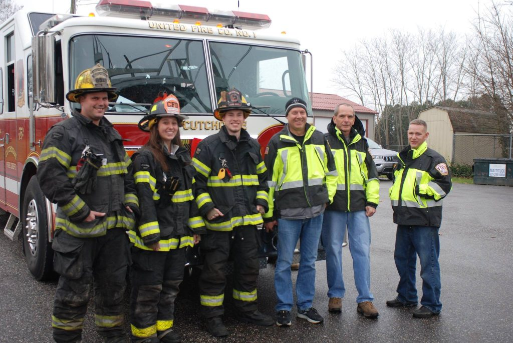 group of firefighters standing in front of fire truck
