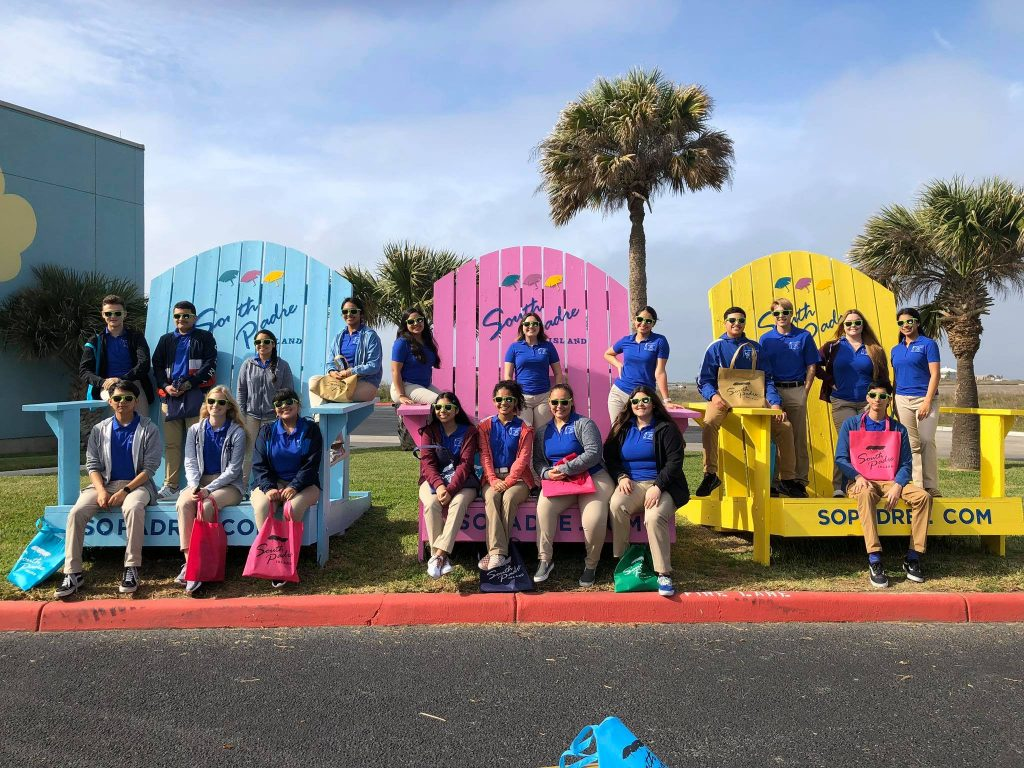 Leadership class group posing on over sized Adirondack chairs