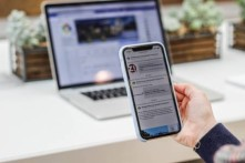 Person holding a phone reading member news