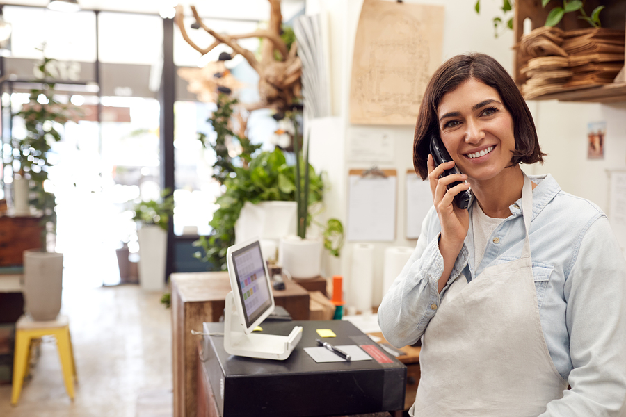 Female Sales Assistant Taking Phone Call Behind Sales Desk Of Florists Store