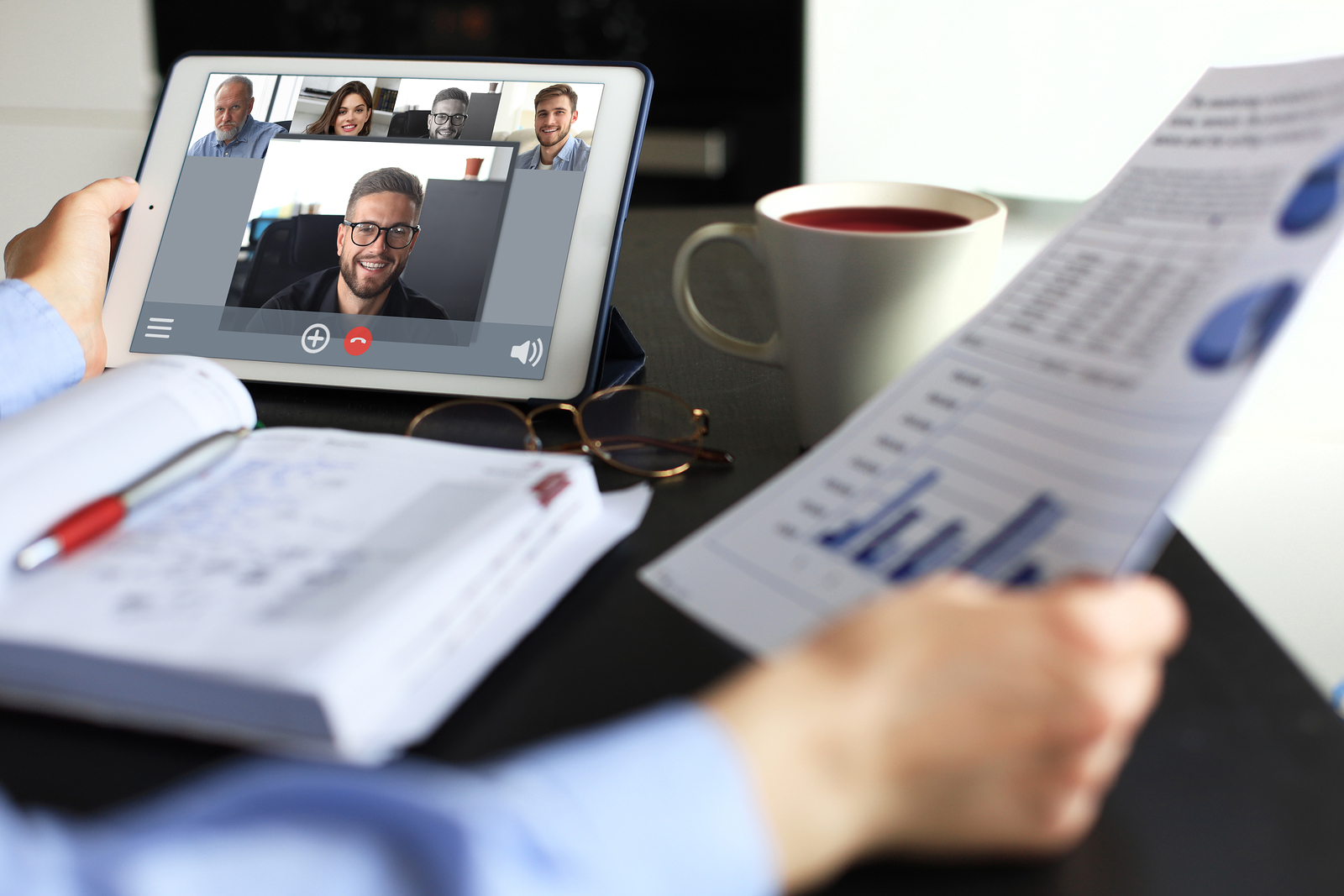 Networking Business woman talking to her colleagues in video conference. Business team working from home using digital tablet.