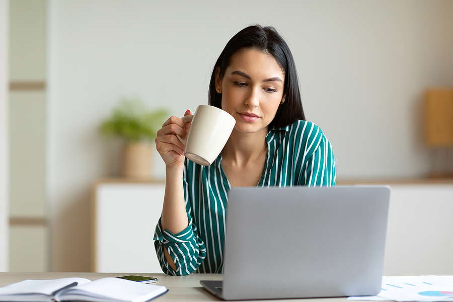 Woman at office laptop coffee
