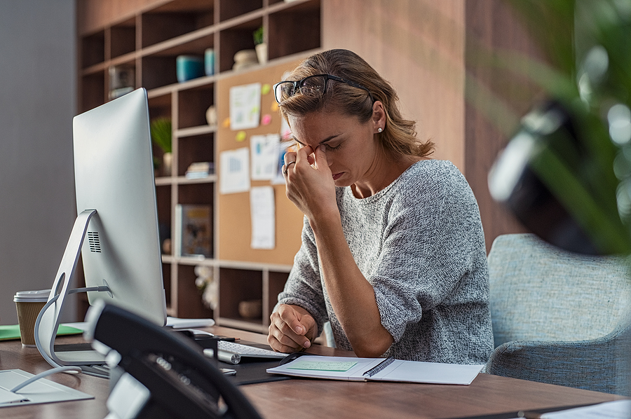 Exhausted businesswoman experiencing workplace stress