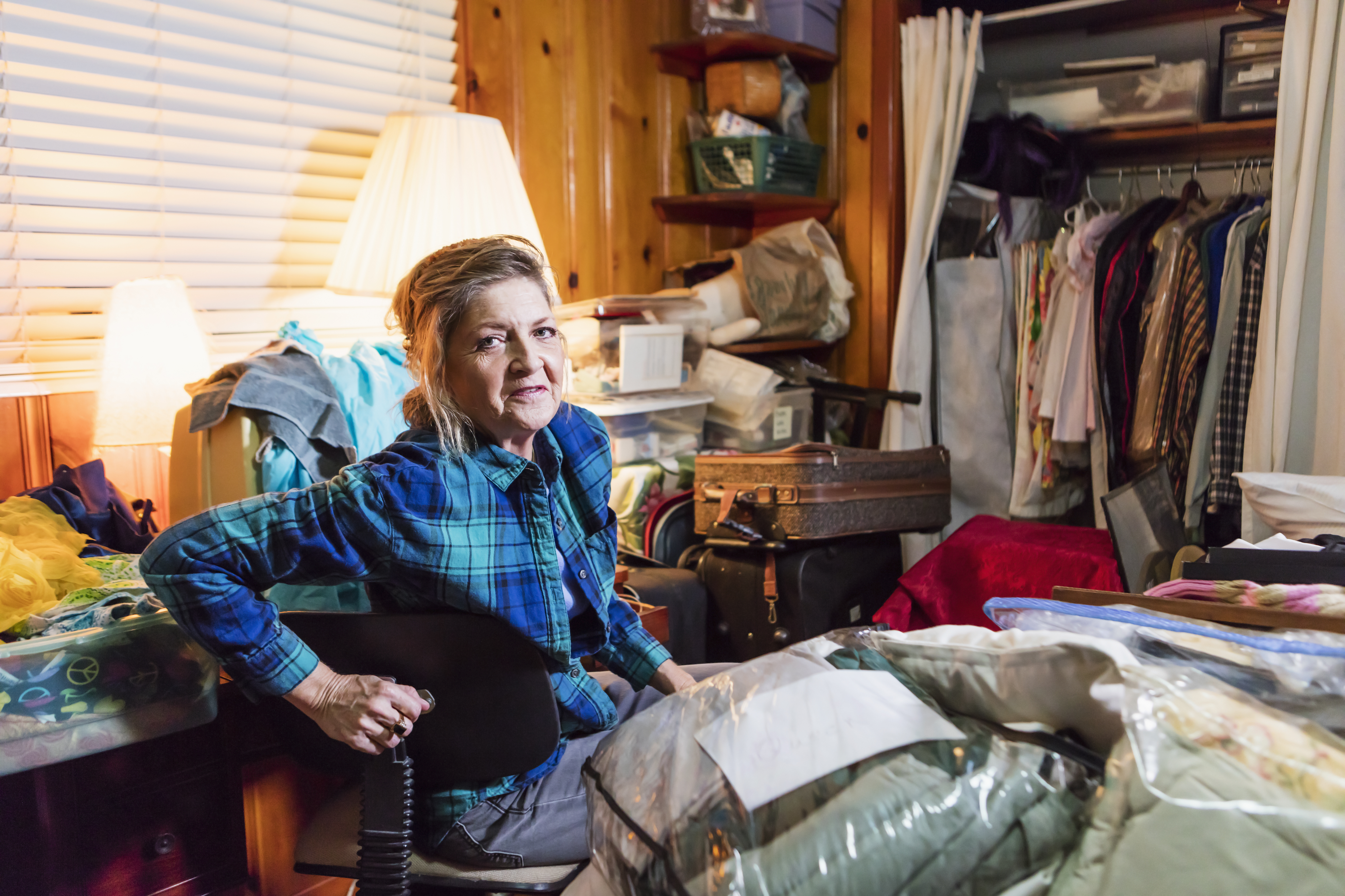 A senior woman in her 60s at home, sitting in a messy, cluttered room, looking at the camera with a serious expression.