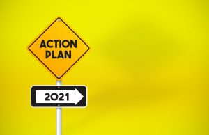 Action Plan 2021 Directional Road Sign On Yellow Background. Horizontal composition with copy space.
