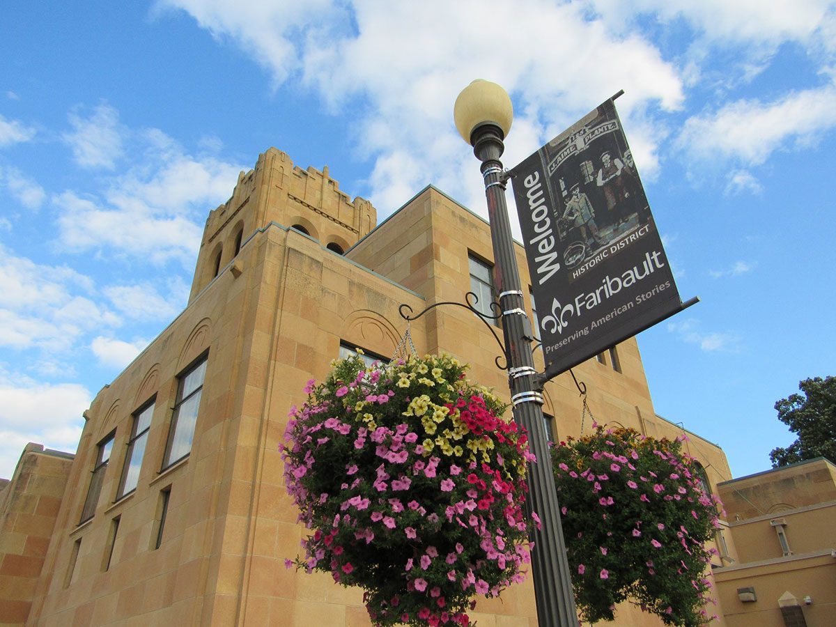 Greek inspired library building with banner on pole in front saying welcome to Faribault, surrounded by flower baskets