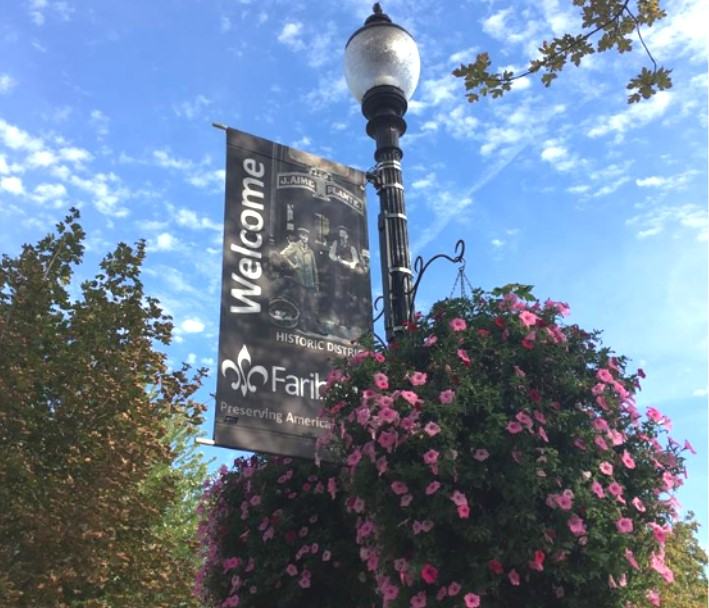 Flower baskets hang from light pole with banner reading welcome to Faribault