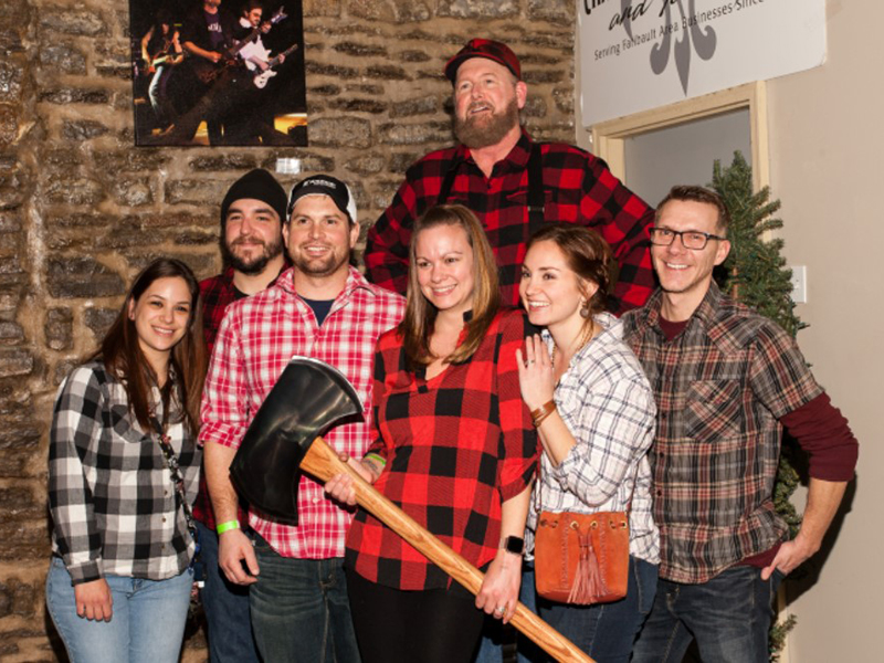 Several people wearing flannel standing together while woman in front holds axe