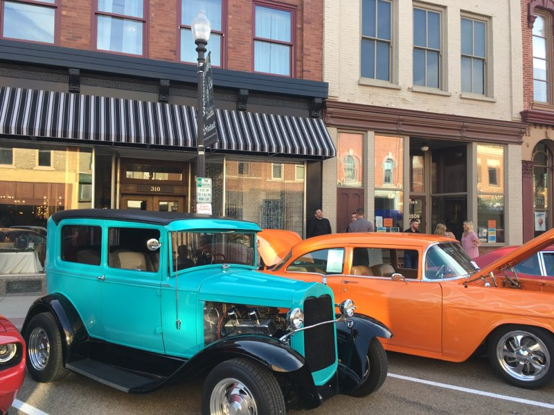 An orange vehicle and a blue vintage vehicle on a historic downtown street