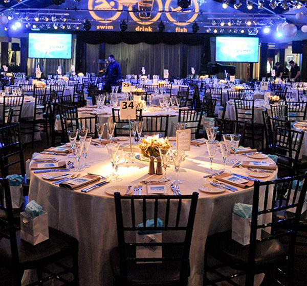 room of tables set for dinner at event
