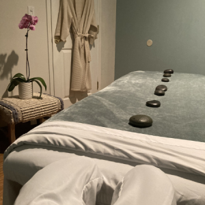 Addison St Spa massage room with hot stones, robe, massage table