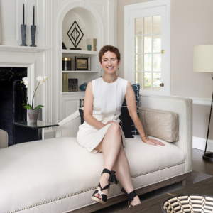 KAM Designers Owner on white couch in white living room