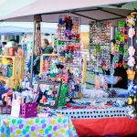 Vendor booth and colorful items for sale at Eggstravaganza
