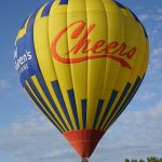 "People riding in a hot air balloon that says ""Cheers"" on the outside of the balloon - Galt Balloon Festival"