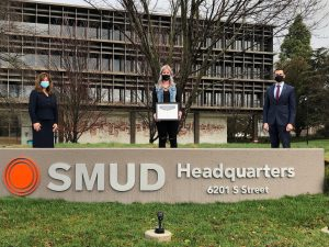 SMUD Feb 2021 Business of the Month photo in front of the SMUD sign with Rachelle Herendeen, Jim Alves and Susanne Dizon
