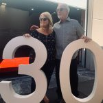 """Photo of Terry Carson, owner of Carson's Coatings standing with her 25 year employe, Bobby Williams next to a large """"30"""" sign (made by Carson's Coatings) for their 30th year in business - June 24 2021"""