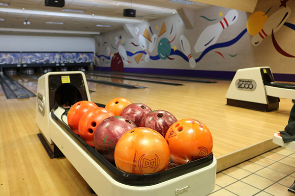 bowling balls on ball return at bowling alley