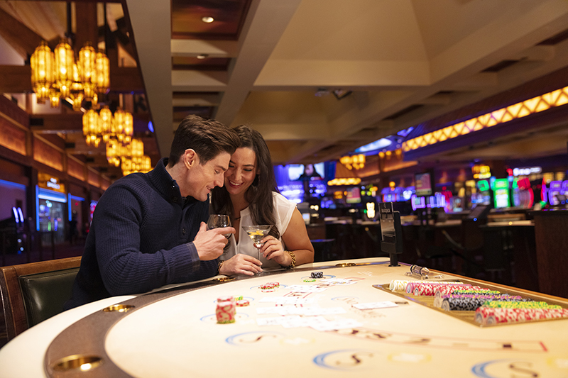 couple at black jack table at casino having a beverage