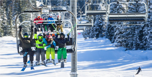 downhill skiers on ski lift