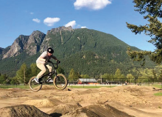 biker on bike trail with mountains in background