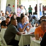 people at tables in discussions under outdoor tent