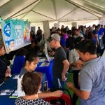 people at job fair in outdoor tent