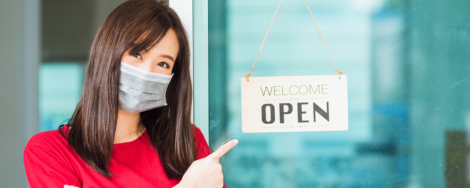 woman with mask on pointing at welcome we are open sign