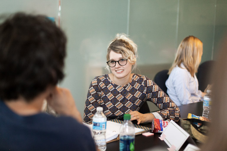 woman working at table smiling at coworkers