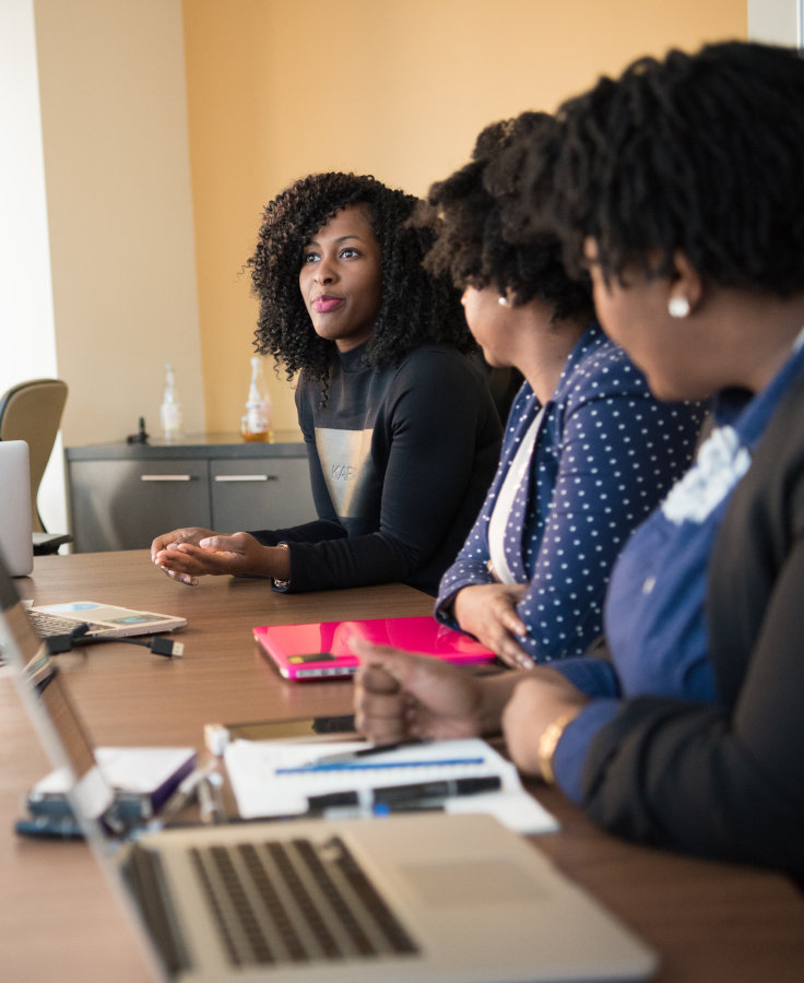 women meeting at a table with laptops