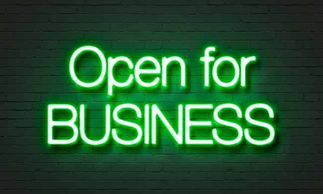 Open for business neon sign on brick wall background