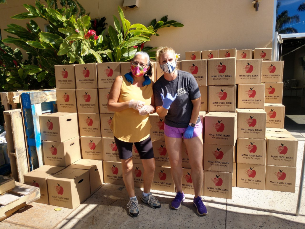 RAM members Rosalind Link (left) and Alana Rucynski help distribute boxes of food drive-thru-style at Hope Chapel in Kihei, one of several large-scale food distribution sites on Maui.