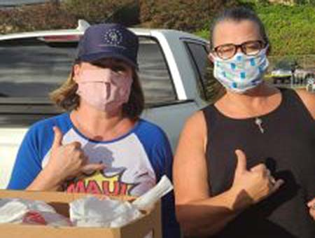 Realtors Association of Maui (RAM) members Melissa Salvador (left) and Gina Duncan are among the many volunteers who have helped distribute boxes of food to residents in need during the Bayanihan food distributions at the Binhi at Ani Filipino Community Center. Photo courtesy Gina Duncan