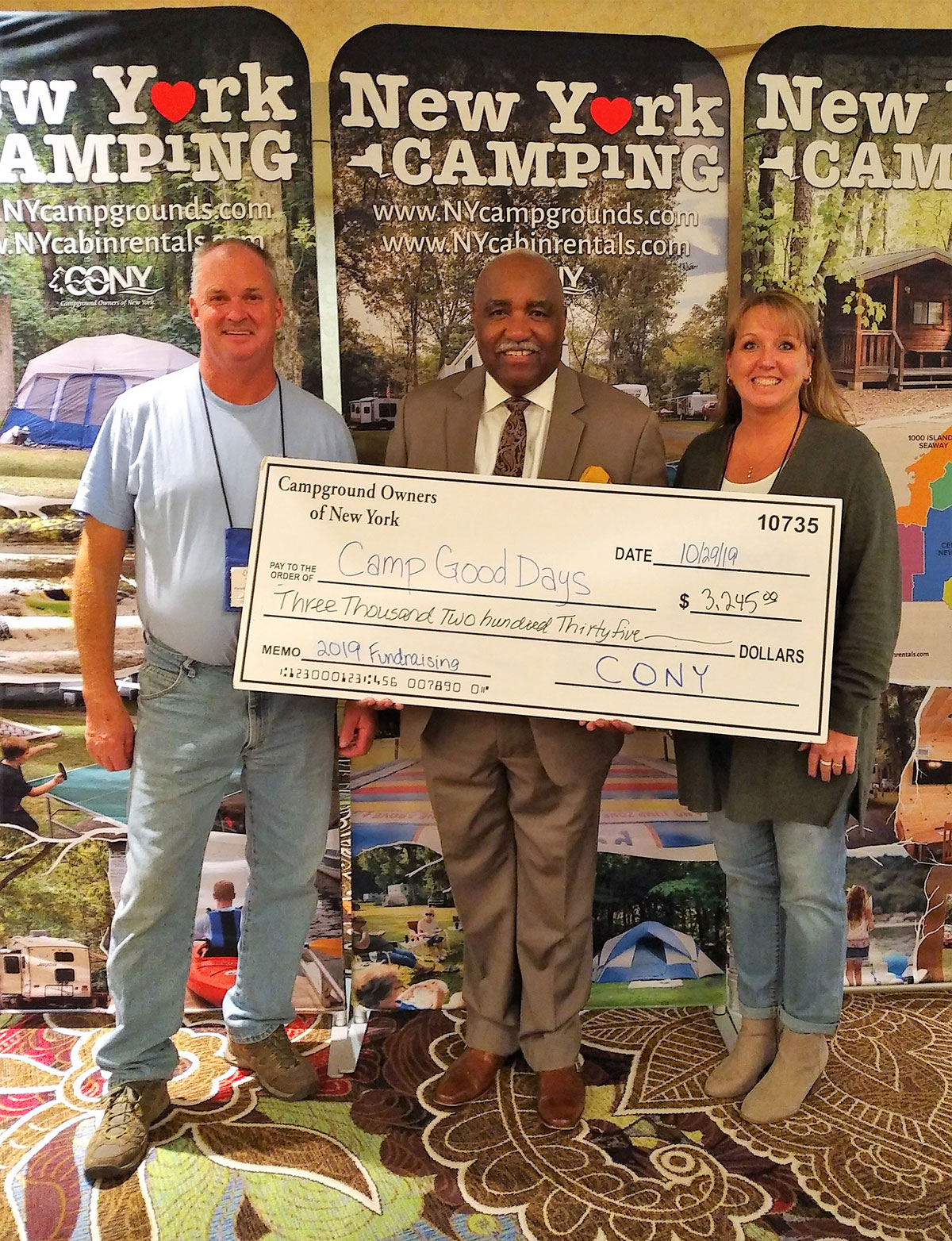 Campground owners pose with Camp Good Days rep and oversize check