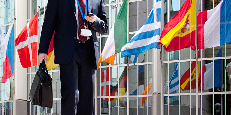 Businessman in suit walks using mobile phone in front of international flags