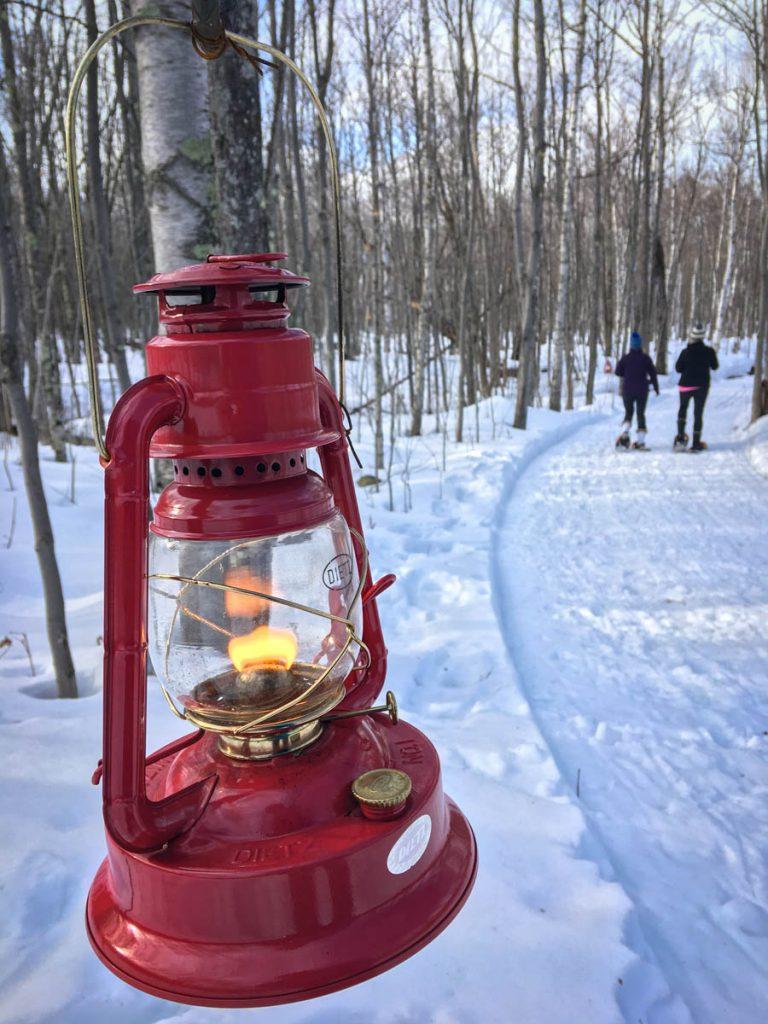 two women snowshoeing on a lantern lit path