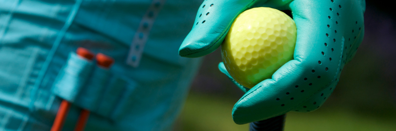 An up close image of a gloved hand placing a golf ball on top of a tee