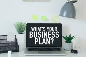 """An open laptop with the phrase, """"What's Your Business Plan"""" displayed on the screen sitting atop a white desk with a variety of office related supplies."""