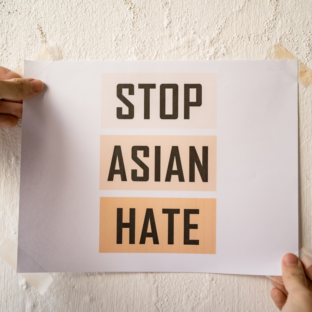 """A white person posting a sign that reads, """"Stop Asian Hate"""""""