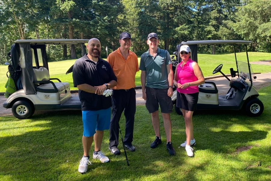 Three men and one woman wearing athletic golf clothing standing side by side looking at the camera and smiling with green grass, evergreen trees, and two golf carts in the background.