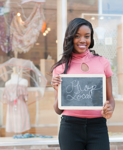 """A young black woman standing in front of a clothing boutique with a sign in her hands that reads, """"Shop Local."""""""