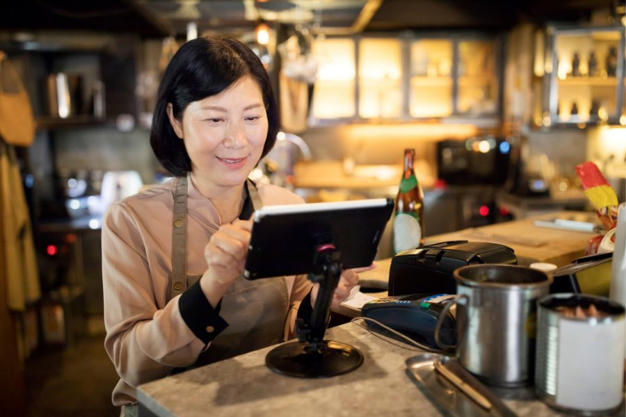 A middle aged asian woman with a slight smile on her face and wearing an apron while interacting with a point of sale system.