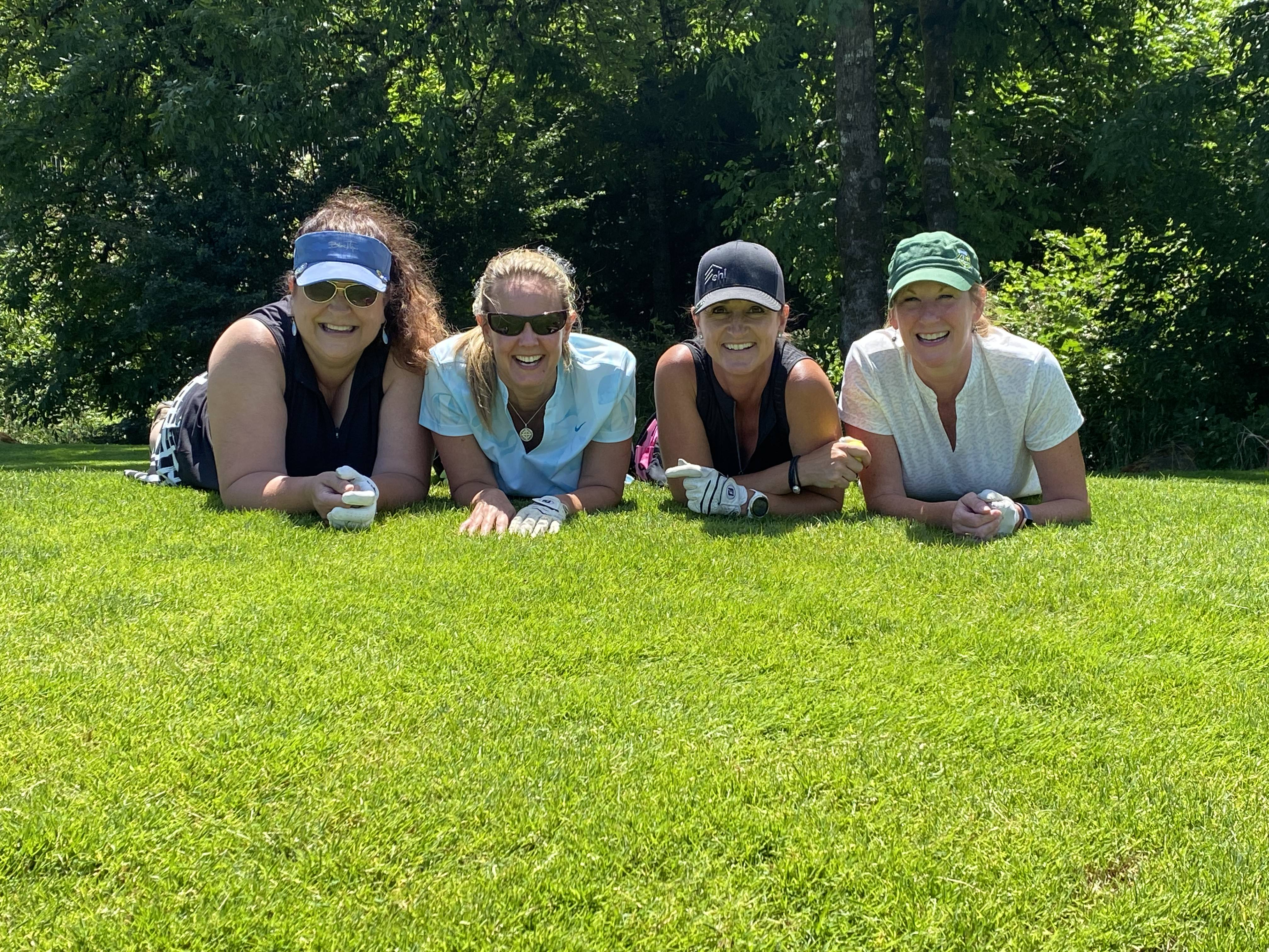 Four white women pose in a row on green grass. They are lying on their stomachs, using their elbows to support them and they are smiling at the camera.