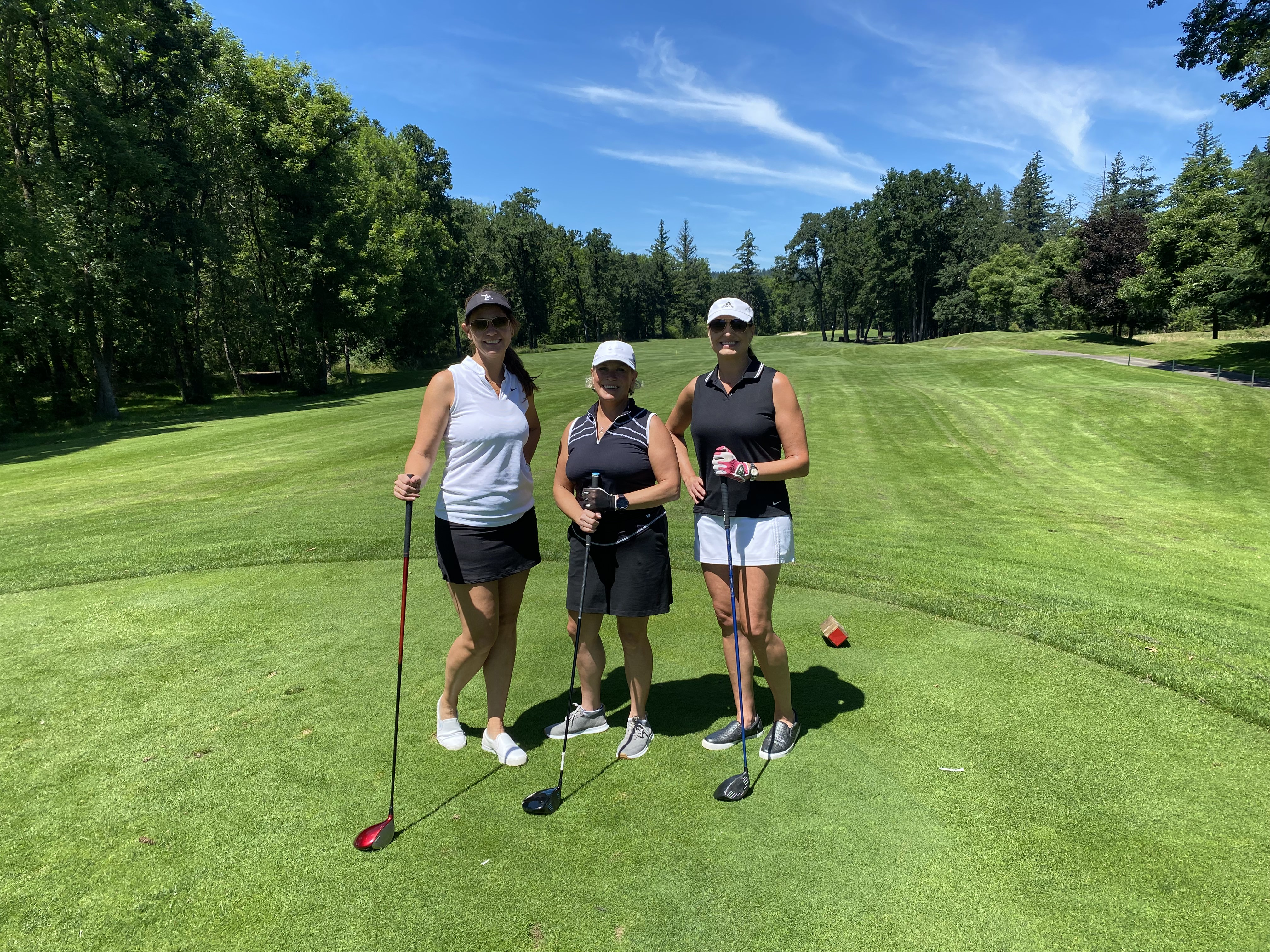 Three women golfers pose on the tee box with their clubs, smiling.